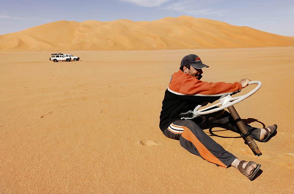 9. Гид по пустыне Калед Дердера с рулем от грузовика, оставшимся после исследовательской команды в п