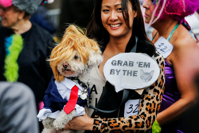A reveller carries her dog which is depicted as Republican U.S. presidential nominee Donald Trump du