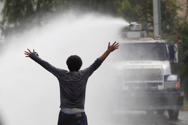 A demonstrator stands in front of a police water canon during a protest to demand justice over the m