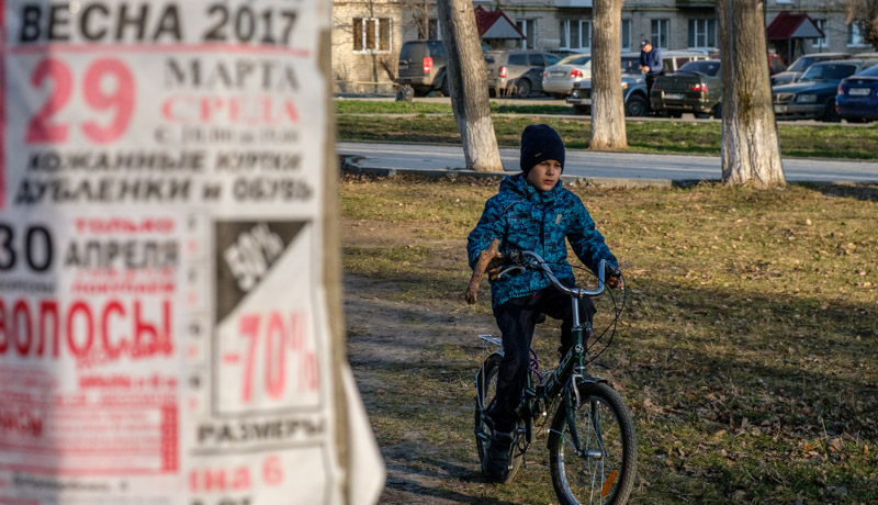 мальчик едет на велосипеде, а на первом плане плакат с надписью весна 2017
