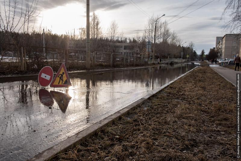 весенний разлив воду в городе, установлены знаки что бы машины не утоноли
