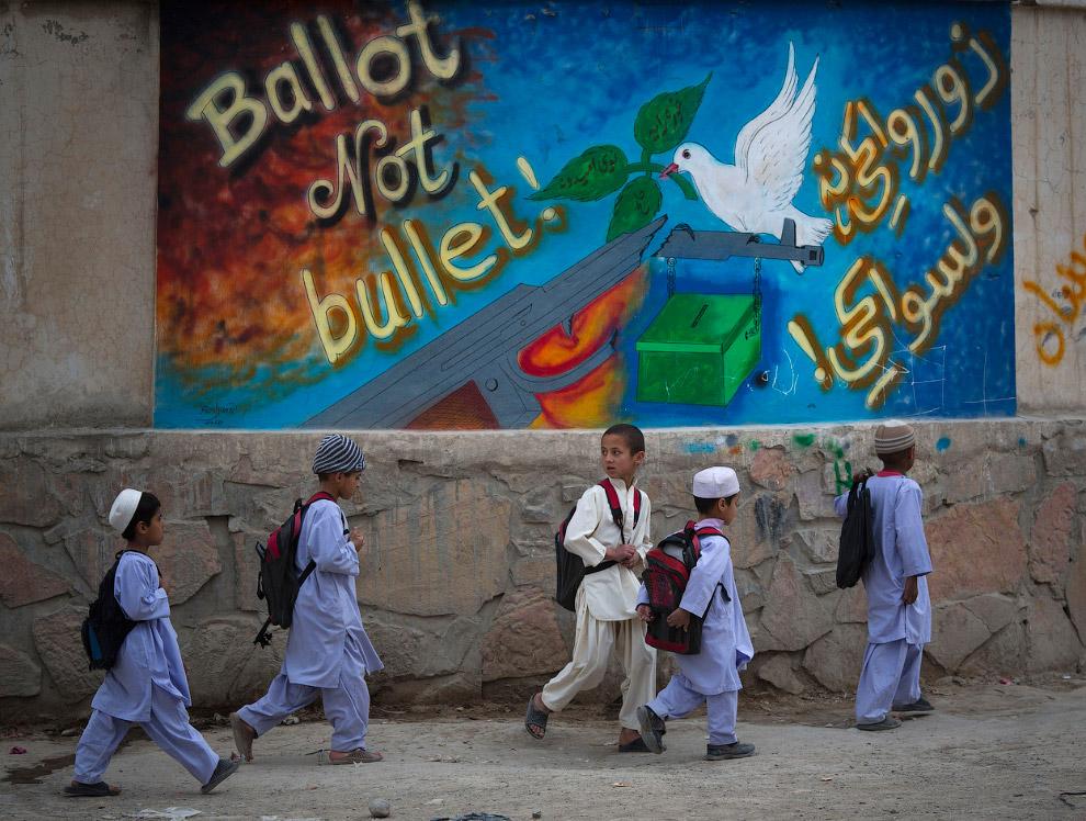 Афганские полицейские на ходу садятся в автомобиль. Талибы напали на штаб избирательной комисси