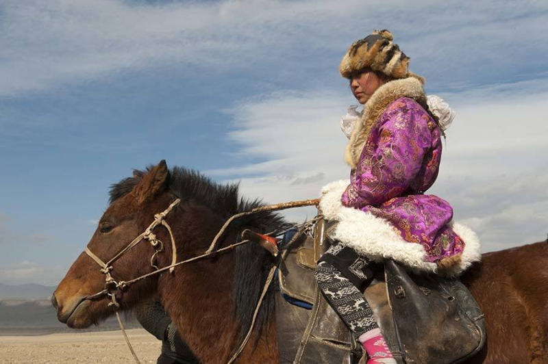 Portrait of a Kazakh teenage girl eagle hunter at the golden Eagle Festival.
