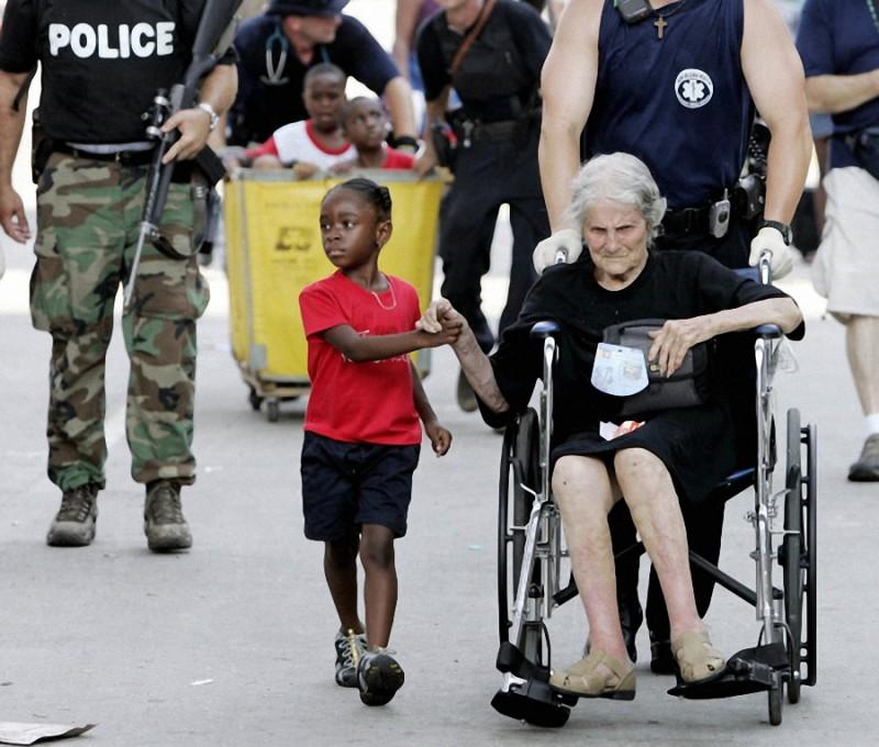27. Таниша Блевин, 5 лет, держит за руку пострадавшую от урагана «Катрина» Ниту Лагард, которой 105