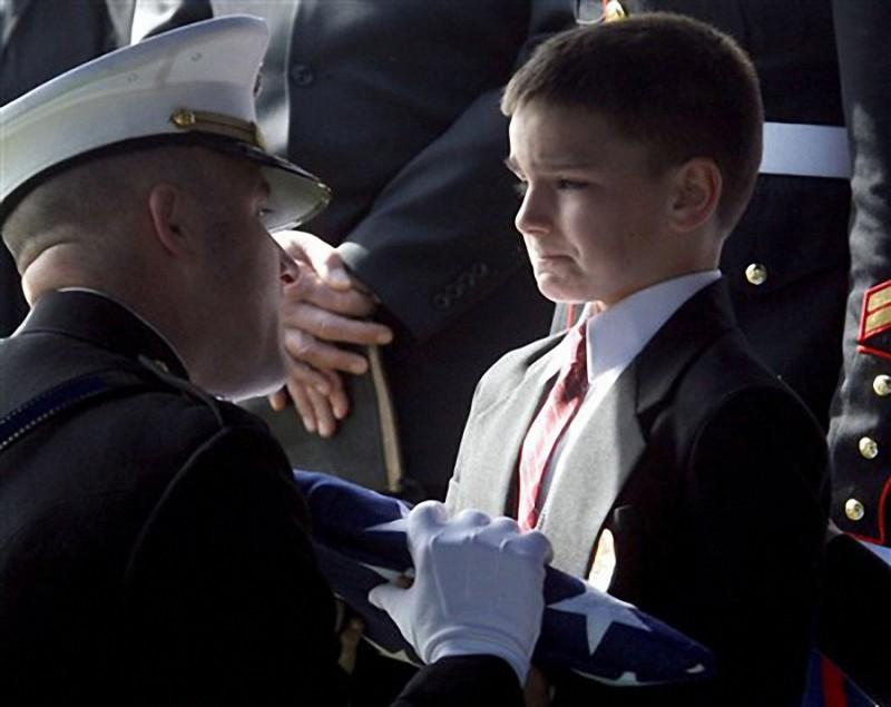 3. Восьмилетний Кристиан принимает флаг во время поминальной службы по своему отцу, который был убит