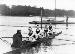 Участники состязаний и тренер в гоночной лодке перед началом состязаний.