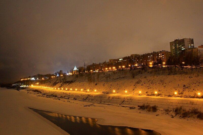 Огни ночной набережной Вятки зимой. Вверху слева телевышка и Александровский сад с ротондой, внизу прогулочная часть набережной, вверху набережная Грина и церковь Феодоровской Богоматери. На льду открытая полынья