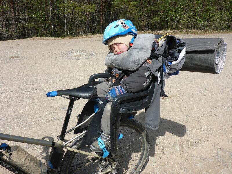 ребенок в походе спит в велокресле с надувной подушкой на шее