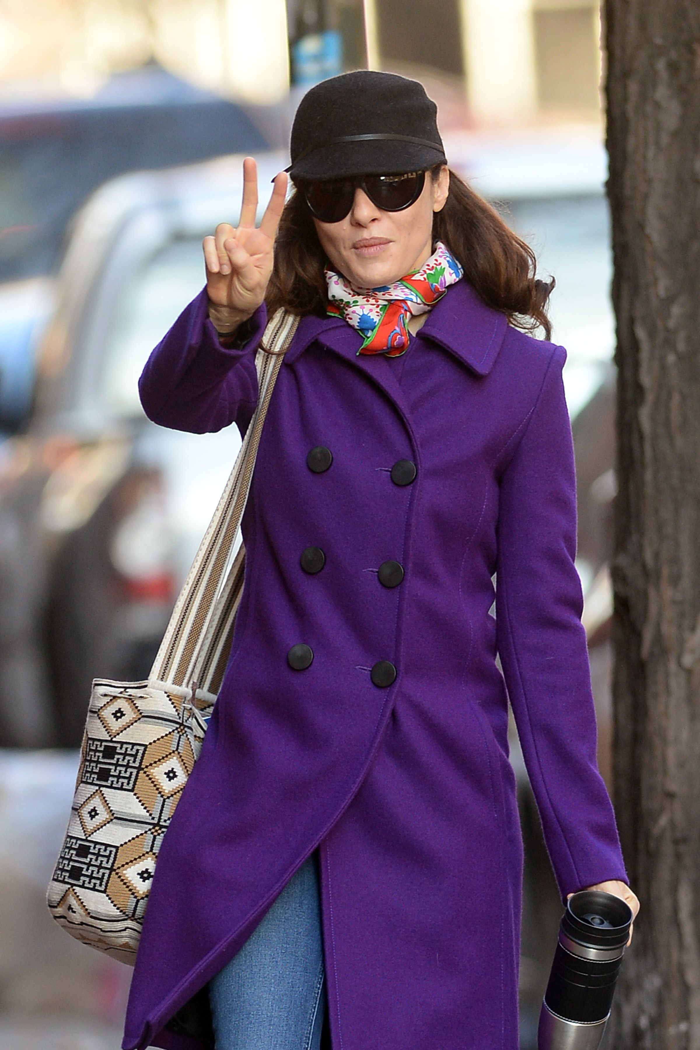 Rachel Weisz Gives The Peace Sign In A Purple Coat