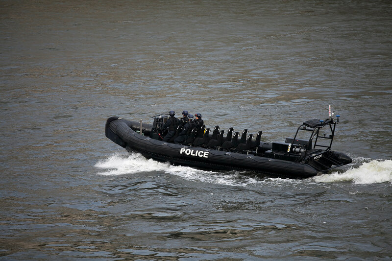 A Metropolitan Police motor launch on the River Thames at the Houses of Parliament, Westminster, London, England, U.K