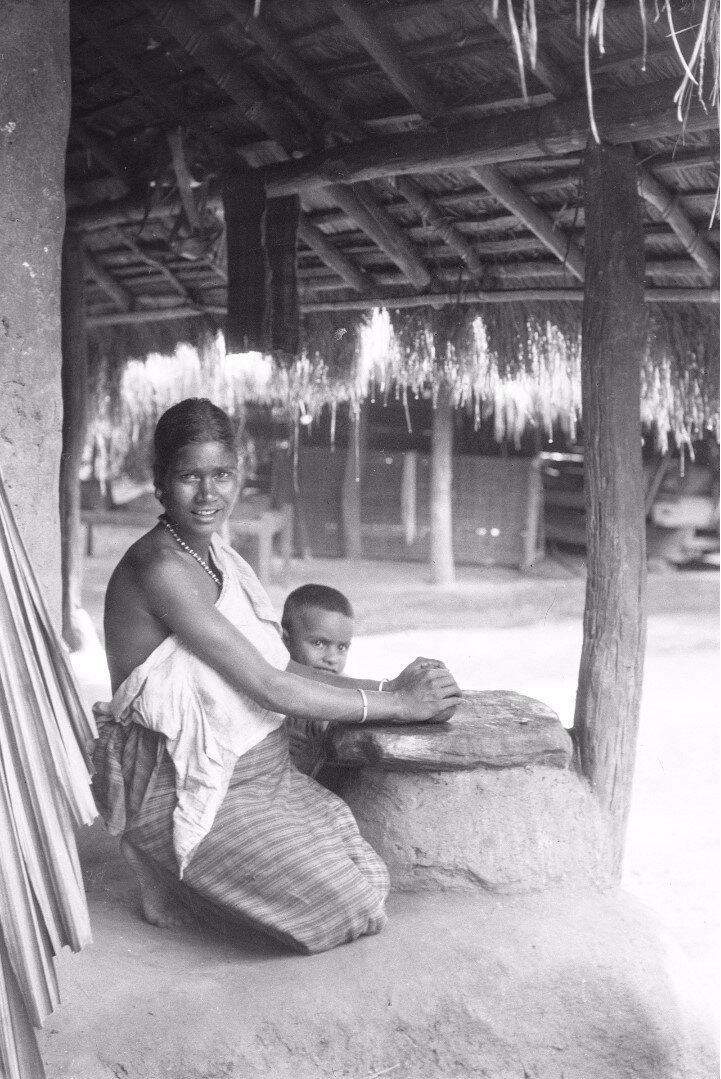 72. Женщина с сыном трут карри на крыльце дома в Моландени
