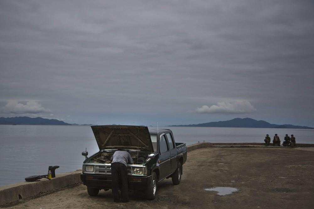 13. Мужчина разбирается с двигателем своего автомобиля рядом с морем в городе Вонсан. (Photo by Davi