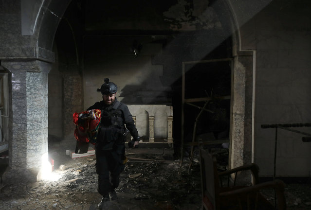 A Christian Iraqi special forces soldier walks in a church in Bartella, east of Mosul, Iraq October