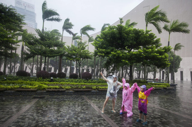 People walk through gale-force winds as Typhoon Haima makes landfall on the South China coast, in Ho