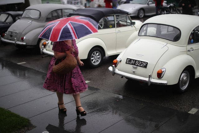 A woman in vintage clothing takes a stroll in the rain past classic Morris Minor cars during Vintage