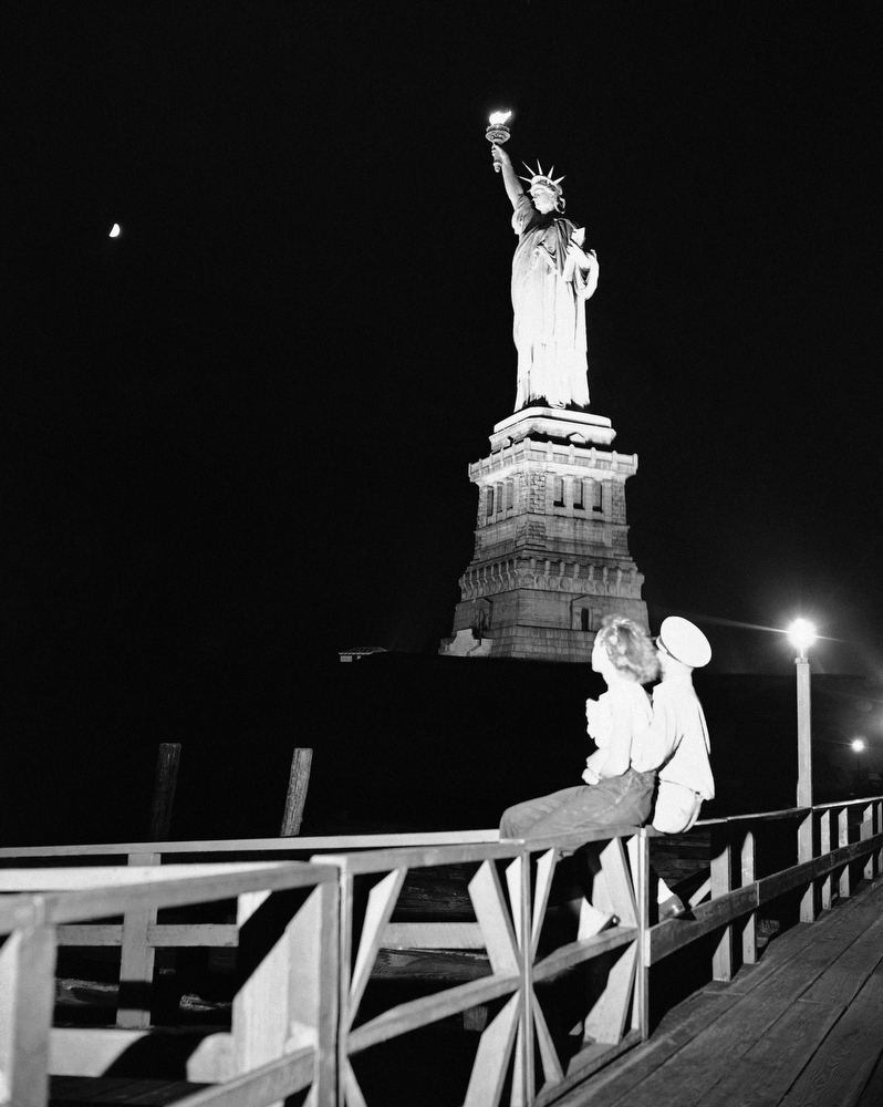 21. Хелен Фостер и Джордж Клэнси сидят на перилах над водой на острове Бедлоу, Нью-Йорк, 2 июля 1949