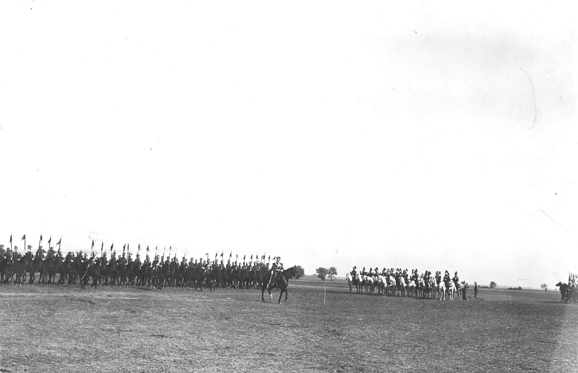 Уланы проходят церемониальным маршем мимо императора Николая II во время парада по случаю празднования 250-летнего юбилея полка