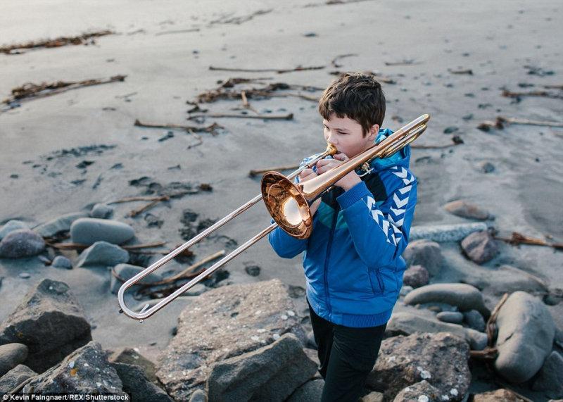 Мальчик играет на тромбоне на побережье в городе Сандавоавур на Фарерских островах в одном из са