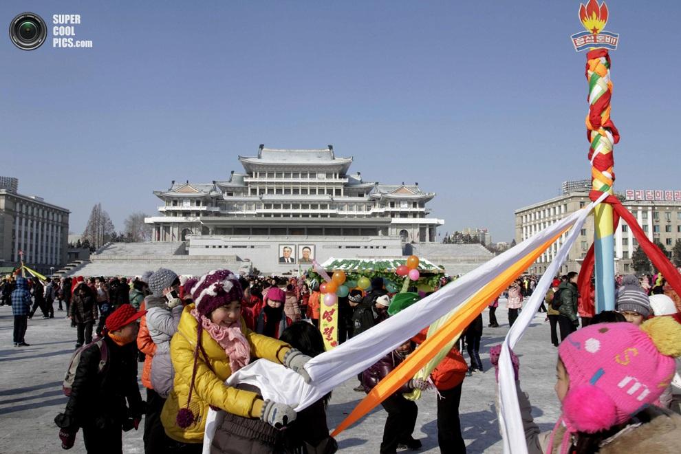 Северокорейские девушки исполняют традиционный танец на площади имени Ким Ир Сена, празднуя Кита