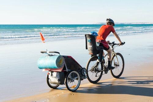 на велосипеде с ребенком по песку с прицепом и велокреслом thule