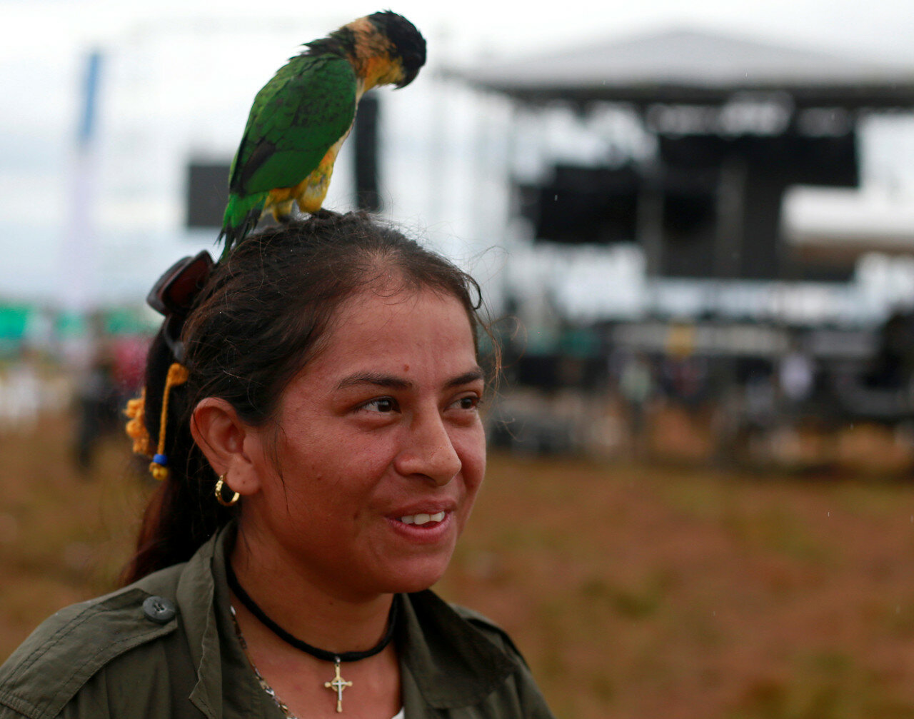 A fighter from Revolutionary Armed Forces of Colombia (FARC), is seen with her parrot after the opening of ceremony congress at the camp where they prepare for ratifying a peace deal with the government, near El Diamante in Yari Plains, Colombia