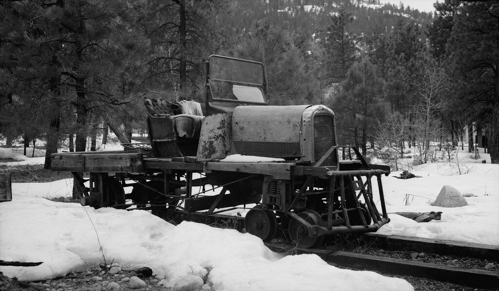 Gas-powered truck engine, hood and seat are mounted on Denver & Rio Grande Western Railroad trucks in Tacoma, La Plata County, Colorado. 1939 March 31.