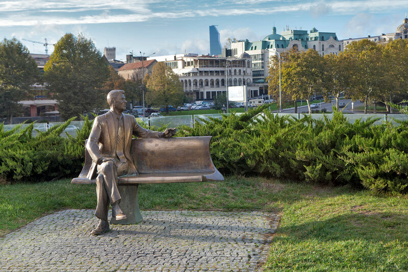 A bronze statue, depicting a smiling Reagan sitting on a bench with crossed legs, can be found in Rike Park.