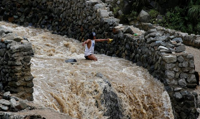 A local miner wades through water as he walks down from a mountain in Benguet a day after Typhoon Ha