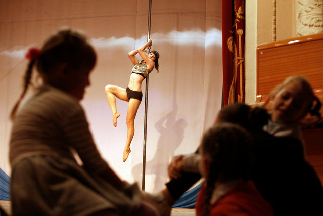 Girls watch as a participant performs during the Perfect Pole 2016 pole dance championship in the so