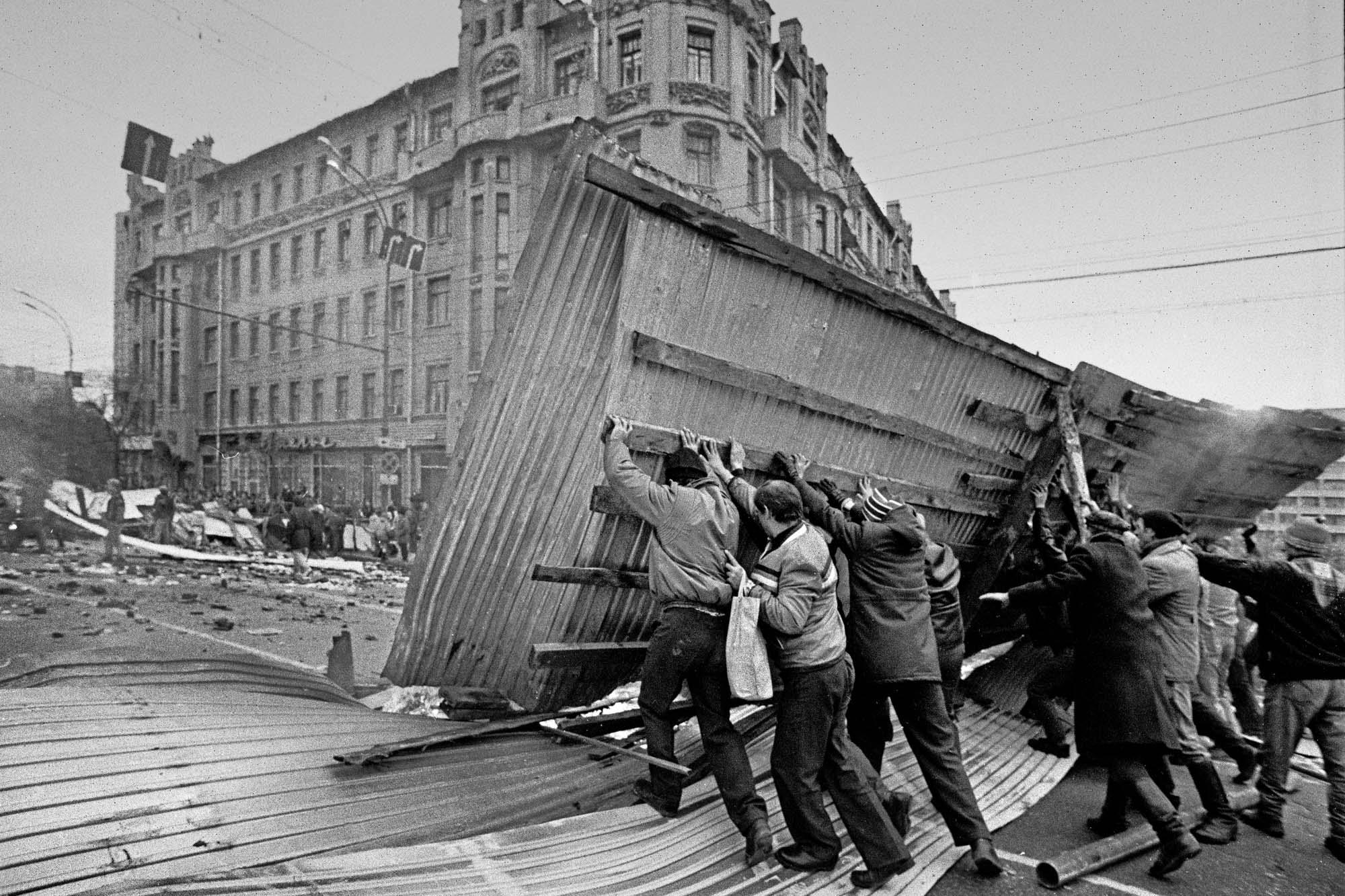 Люди поднимают баррикады 2 октября на Смоленской площади на Садовом кольце