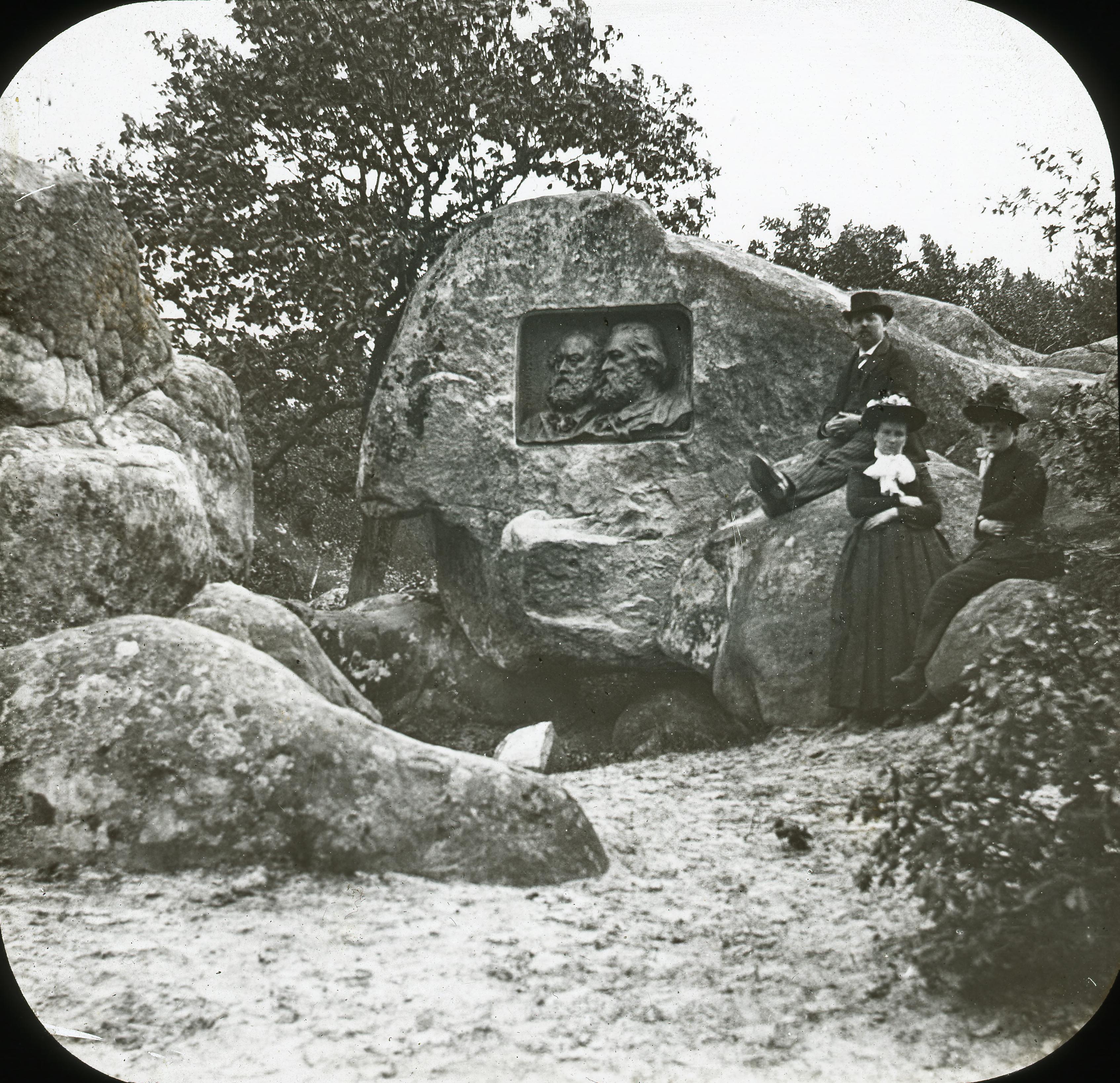 Женщины и мужчина позируют у портрета Милле и Руссо, вырезанного в камне. Лес Фонтенбло