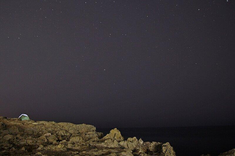 Палатка и камни скал на берегу Чёрного моря ночью среди звёзд (Севастополь, Крым)