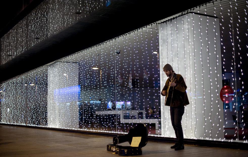 4. Мужчина играет на гитаре перед гирляндами в Памплоне. (AP / Alvaro Barrientos)