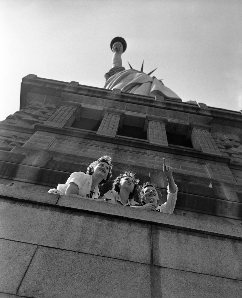 20. Трое туристов из Детройта, Мичиган, смотрят на Манхэттен из-под статуи Свободы, 12 июля 1948 год