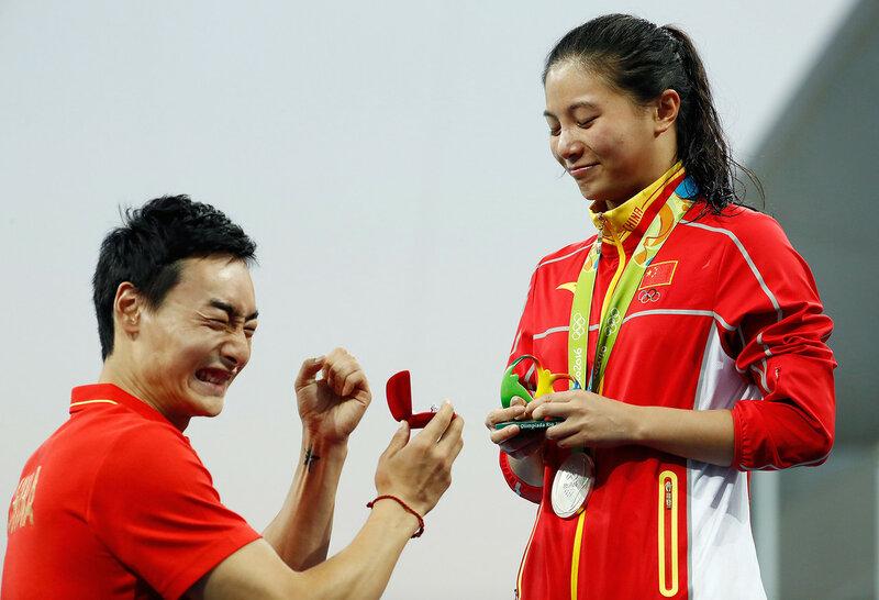 Китайский прыгун в воду делает предложение своей возлюбленной во время церемонии награждения на Олимпийских играх в Рио 14 августа 2016 года. (Clive Rose / Getty)