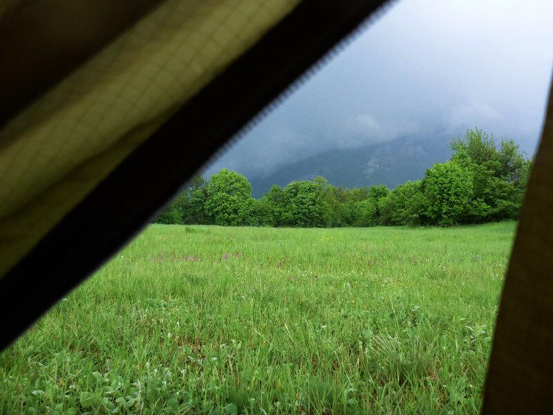 вид из палатки на луг и горы в походе