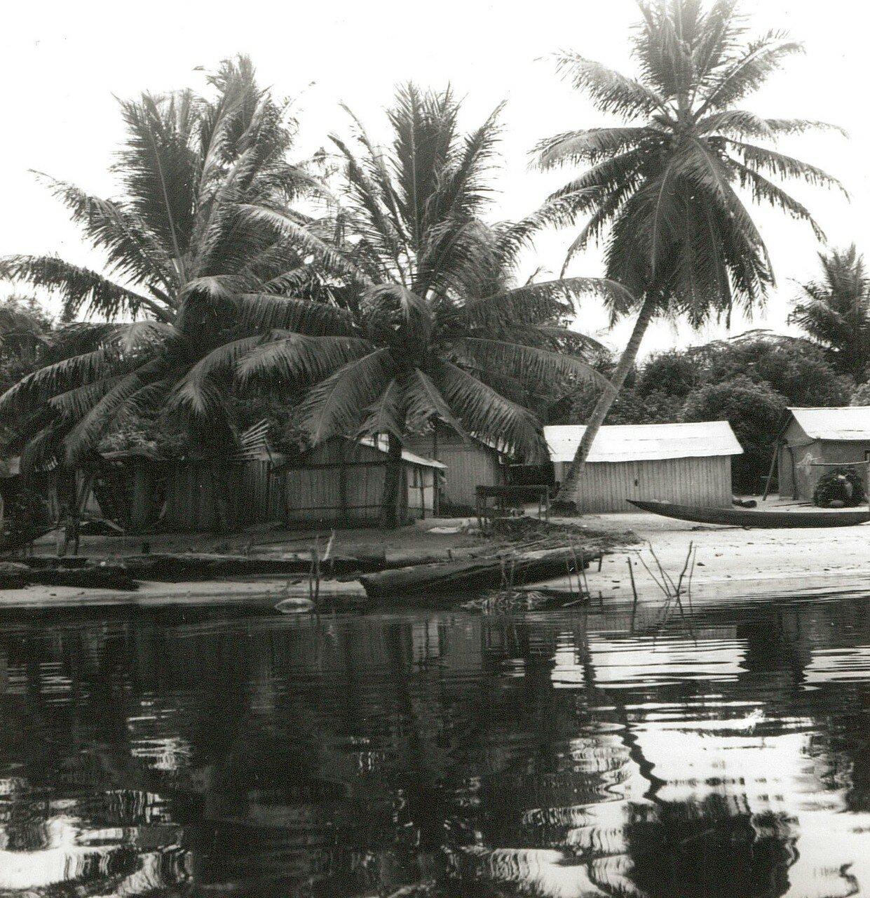 Абиджан. Остров Буле в лагуне  Эбрие. Байдарки и деревянные хижины под кокосовыми пальми