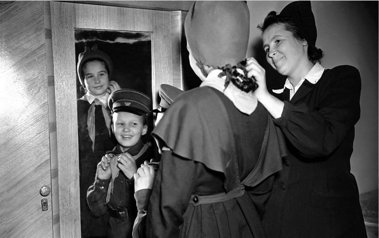 Челябинск. Школа-интернат № 2. Воспитательница 4-а класса Р. И. Селюгина помогает Саше Рябоконову и Нине Выденякиной приготовиться к встрече с родными (1955)
