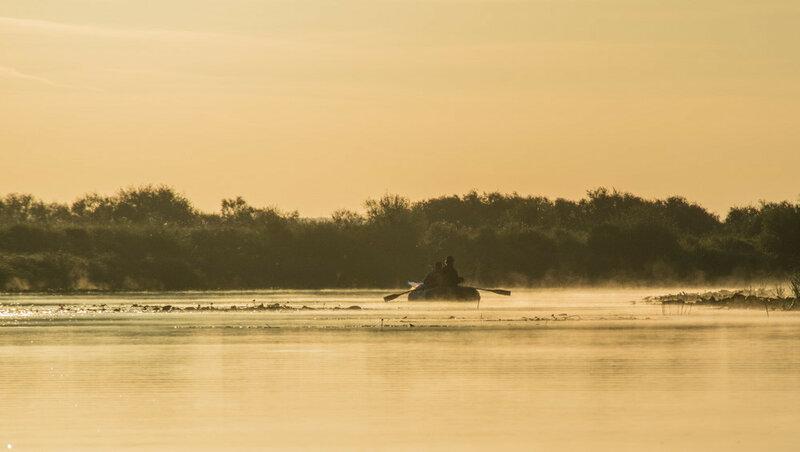 рыбаки в лодке во время восхода солнца на реке