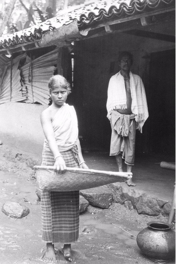 65. Девушка с тазом риса возле дома в Моландени