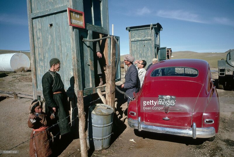 Mongolian drivers fill up their red car at a makeshift gas station in Arbay Heere, Mongolia.jpg