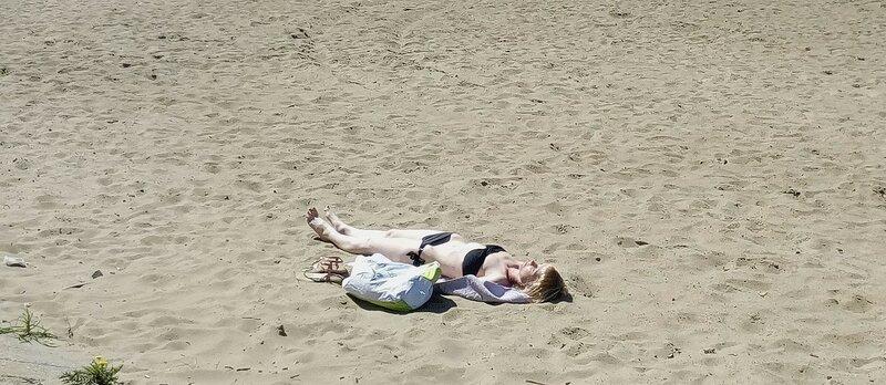 Загорающая на майском пляже