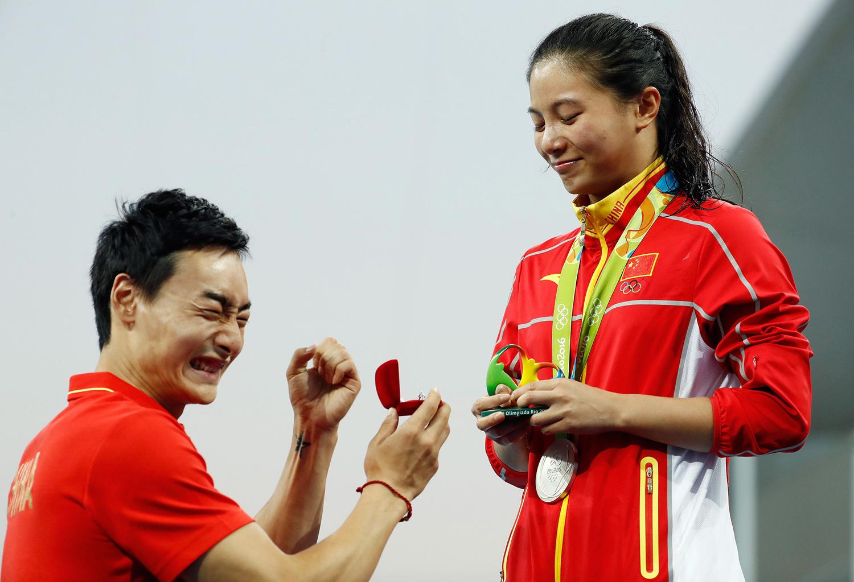 15. Китайский прыгун в воду делает предложение своей возлюбленной во время церемонии награждения на