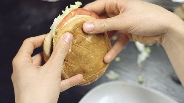 Вот так надо держать гамбургер, чтобы салат не вываливался и соус не закапал весь стол.