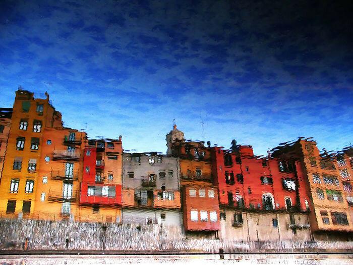 Отражение города в луже похоже на картину