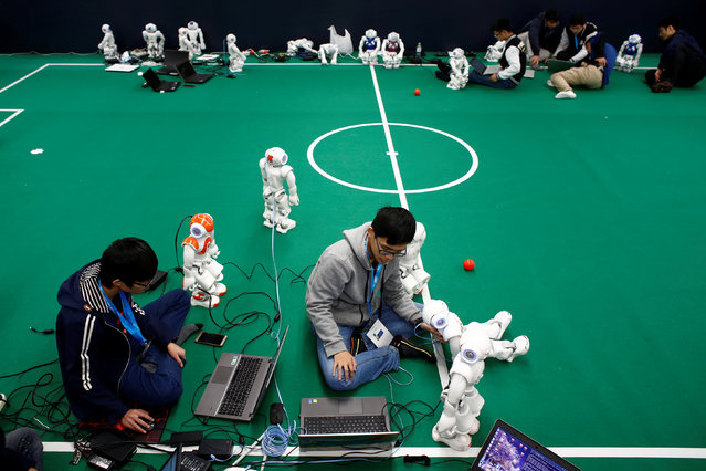 People program NAO robots to prepare them for a robot soccer competition at the WRC 2016 World Robot