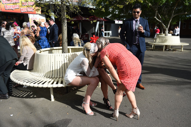 Race goers whisper to each other after the Geelong Cup on Geelong Cup day at Geelong Racecourse in M