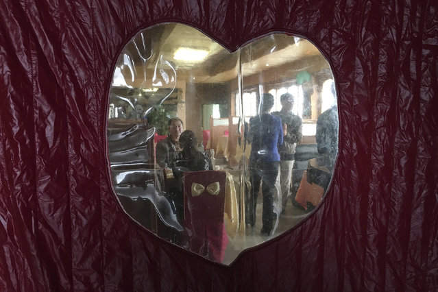 Diners are seen through a door curtain of a local restaurant during lunch hour in Pyongyang, North K