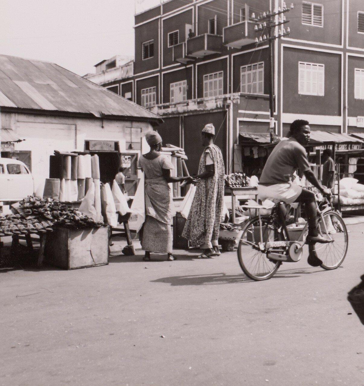 Гана. Такоради. Велосипедист проезжает мимо уличных торговцев