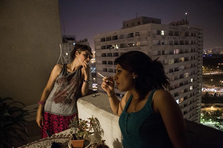 10. Девушки курят на балконе. Дома они могут безнаказанно носить майки и не покрывать голову.